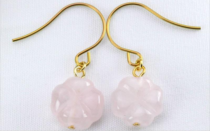 淡いピンク色の「ローズクオーツ」、デザインは四つ葉のクローバー、素材は、アレルギー対応の純チタン