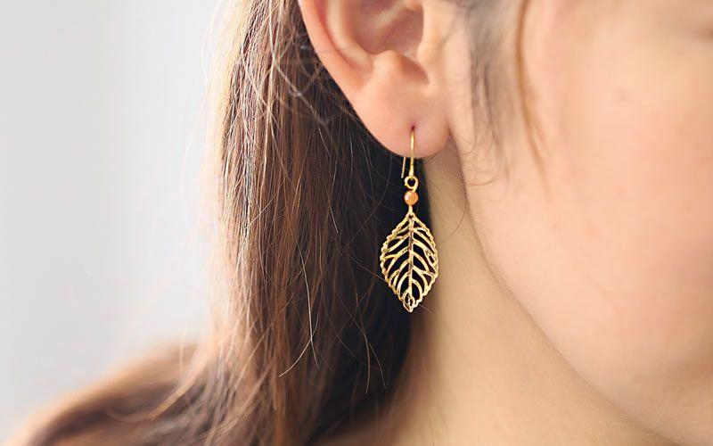 純チタン使用の「Gold leaf / 透かし木の葉のフックピアス」を耳につけた女性の画像